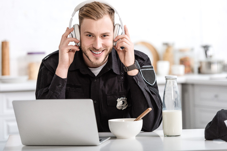 smiling police officer having breakfast and listening to music with headphones at kitchen table