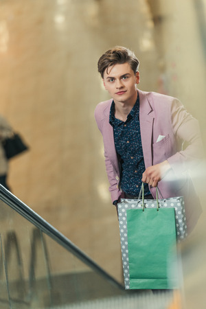 stylish man on escalator with bags at shopping mall Banco de Imagens