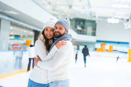 portrait of happy couple looking at camera while hugging on skating rink