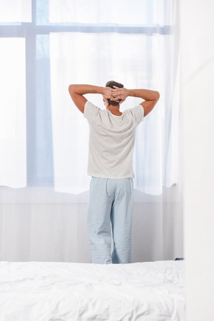 Back view of man standing in sleepwear in room