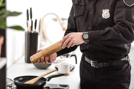 Cropped view of police officer cooking breakfast at kitchen