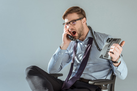 Young annoyed businessman yelling while talking on phone isolated on grey