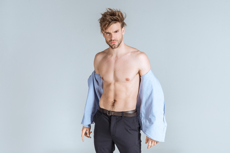stylish businessman with messy hair taking off his shirt, isolated on grey