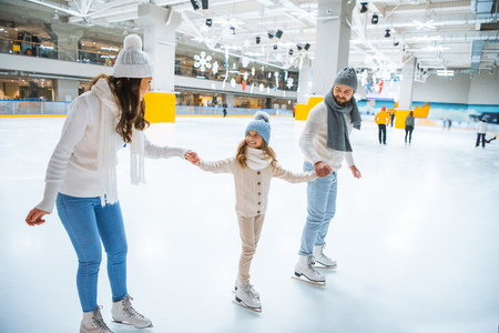 happy family holding hands while skating together on ice rink