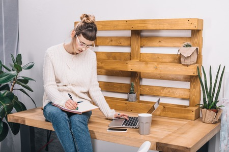 girl sitting on table in office and writing something to notebook Stock Photo