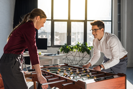 happy businesspeople playing kicker at modern office