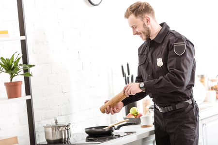 Police officer peppering breakfast at stove in morning