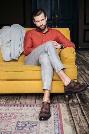 Elegant man in suit and brogue shoes sitting on yellow sofa Stock Photo