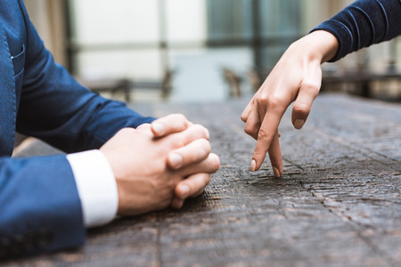 Cropped shot of woman making steps with fingers to her boyfriend