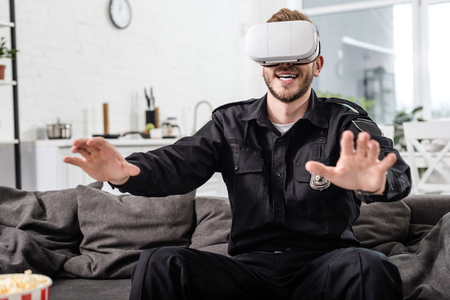 Policeman with virtual reality headset on head playing video game on couch