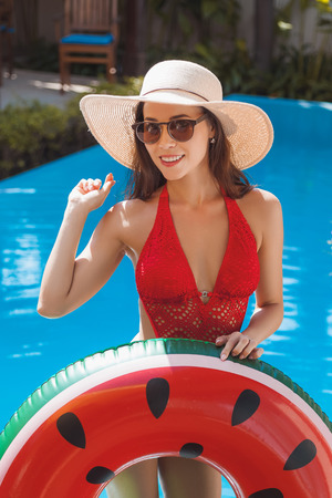 Happy young woman in swimsuit with inflatable ring at poolside Stock Photo