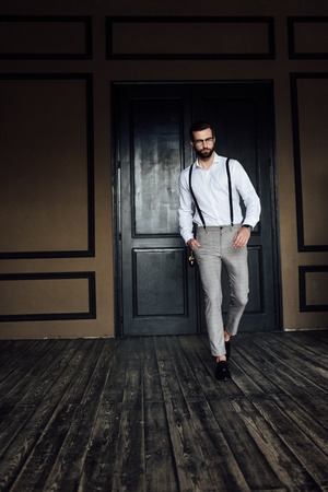 Stylish elegant man posing in trendy suspenders against door in loft interior