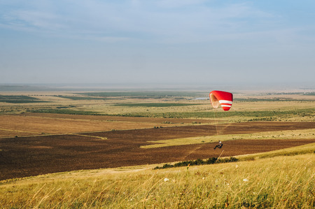 Parachutist flying over beautiful nature of Carpathians, Ukraine.