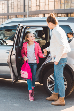 Daughter getting out from car and holding hand of mom