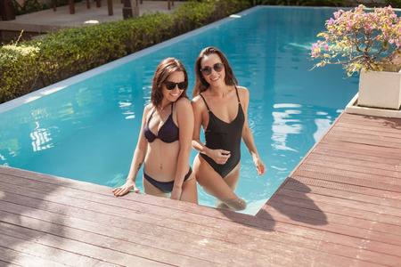 Attractive young women in bikini and swimsuit standing in swimming pool