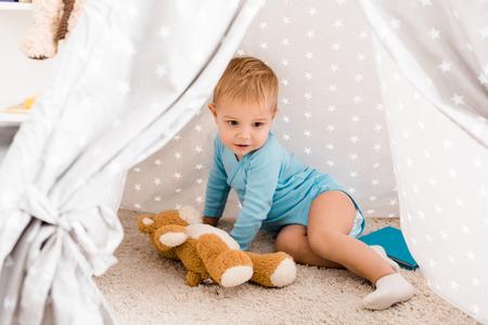Cute toddler boy in blue bodysuit sitting on carpet in baby wigwam