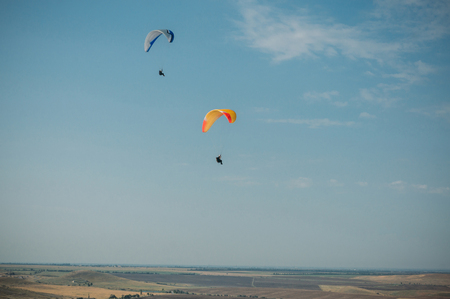 Parachutes in the sky over field in hillside area of Crimea, Ukraine. Stock Photo