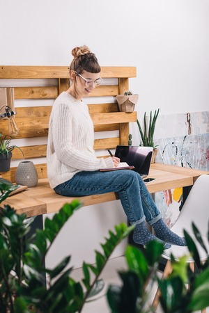 Smiling girl sitting on table in office and writing something to notebook