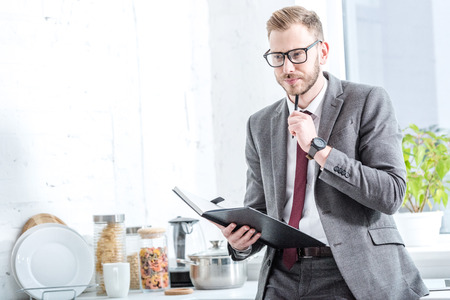 Pensive businessman holding notebook and pen at kitchen
