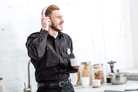 Handsome policeman drinking coffee and listening to music with headphones at kitchen