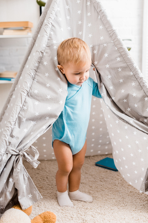 Cute toddler boy in blue bodysuit standing in grey baby wigwam on carpet