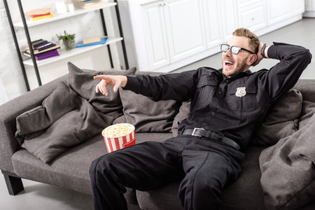 Policeman in 3d glasses sitting on couch and  watching movie 写真素材