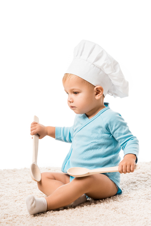 Close up view of toddler boy in bodysuit and chefs hat sitting on carpet and holding two big wooden spoons isolated on white