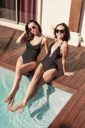 Attractive young women in swimsuits sitting at poolside with legs in water