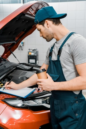 Auto mechanic with disposable cup of coffee making notes at automobile with opened cowl Stock Photo