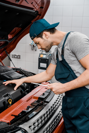 Side view of auto mechanic with tablet checking car cowl at mechanic shop Stock Photo - 112748073