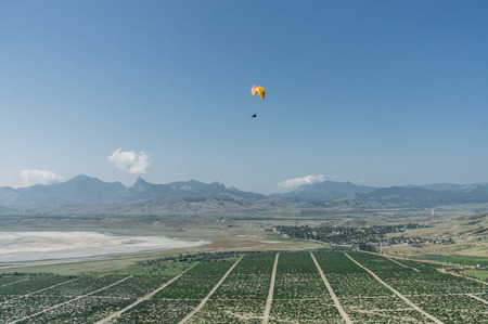 Mountainous landscape with paratrooper flying in the sky, Crimea, Ukraine.