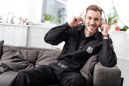 Smiling police officer sitting on couch and listening to music with headphones 写真素材 - 112748011