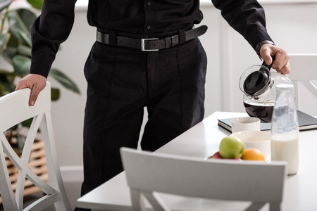 Partial view of policeman pouring filtered coffee from glass pot at kitchen