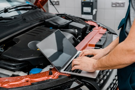 Cropped shot of auto mechanic working on laptop with blank screen at automobile with opened car cowl at mechanic shop