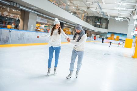 Man teaching girlfriend how to skate on ice rink Stockfoto