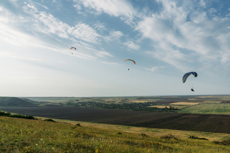 Parachutists gliding in blue sky over scenic landscape of Crimea, Ukraine.