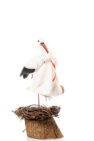Decorative stork holding in beak baby nappy and standing in wicker nest isolated on white Banco de Imagens