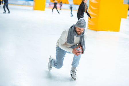 Man injured knee while skated on ice rink Archivio Fotografico - 112748326