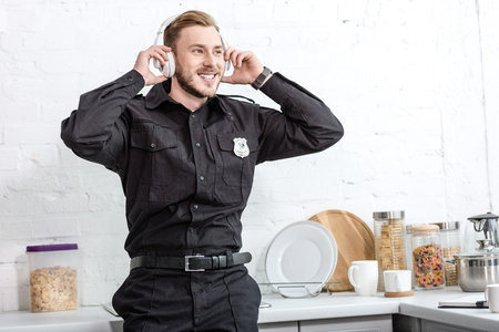 Handsome policeman listening to music with headphones at kitchen 写真素材
