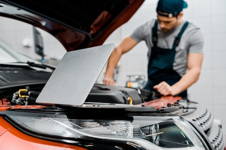 Selective focus of laptop and auto mechanic at auto repair shop Stock Photo - 112748347