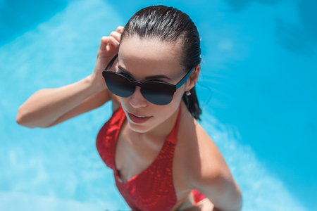High angle view of young wet woman in swimsuit at swimming pool