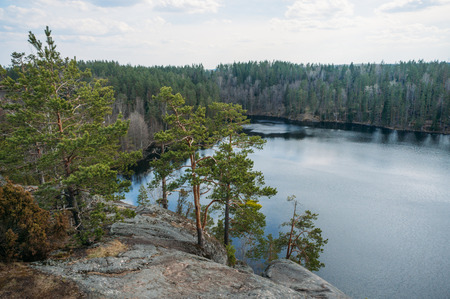 View of rocky slope of cliff with trees over lake water, Karelian Isthmus, Russian Federation