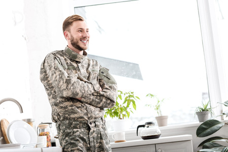 smiling army soldier with arms crossed in kitchen Stock Photo