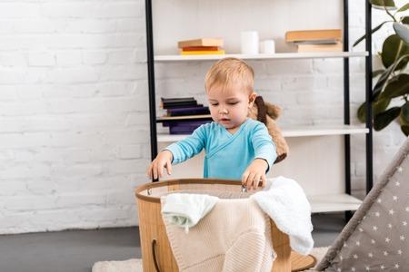 cute baby in blue bodysuit standing near wicker laundry basket in room