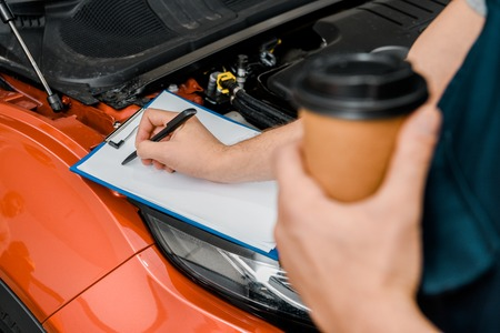 cropped shot of male auto mechanic with disposable cup of coffee making notes at automobile with opened cowl Stock Photo