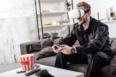 policeman with virtual reality headset on head holding gamepad, sitting on couch and playing video game