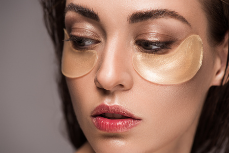 beautiful girl with collagen eye pads, isolated on grey