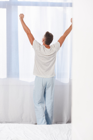 Back view of man standing in pyjamas in room