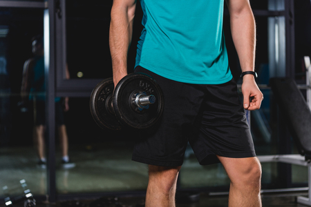 cropped view of muscular sportsman holding dumbbell in gym