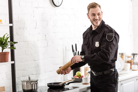 police officer smiling and cooking breakfast at kitchen